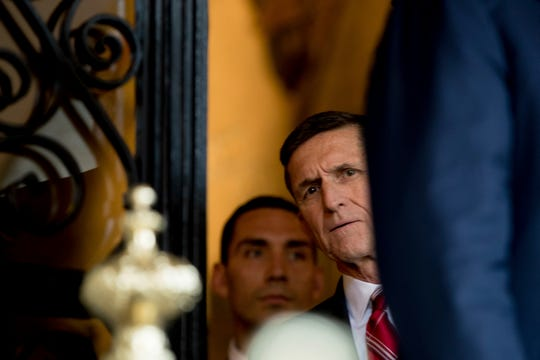 FILE - In this Dec. 21, 2016, file photo, retired Gen. Michael Flynn, a senior adviser to then-President-elect Donald Trump listens as Trump speaks to members of the media at Mar-a-Lago, in Palm Beach, Fla. (AP Photo/Andrew Harnik, File)