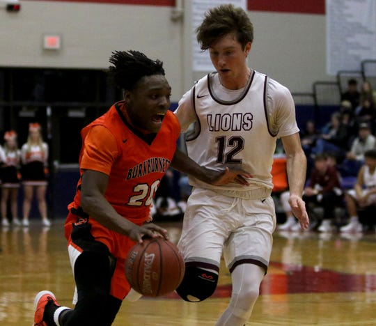 Burkburnett's KenDarious Horton dribbles by Brownwood's John Wilhelm Friday, Feb. 22, 2019, in the Region I-4A area playoff in Graham. The Bulldogs defeated the Lions 87-68.