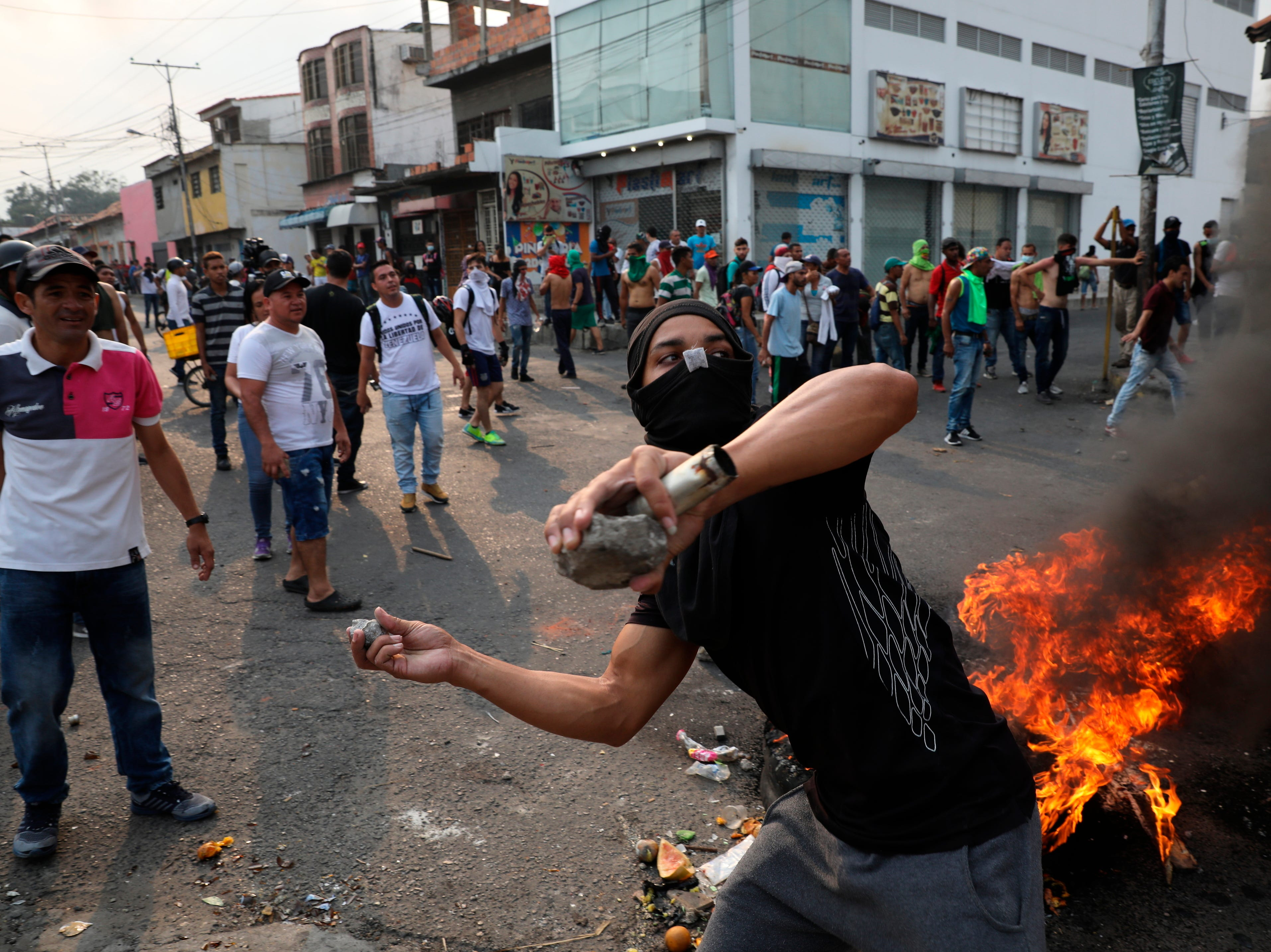 A demonstrator throws rocks during clashes with the Bolivarian National Guard in Urena, Venezuela, near the border with Colombia, Saturday, Feb. 23, 2019. Venezuela's National Guard fired tear gas on residents clearing a barricaded border bridge between Venezuela and Colombia on Saturday, heightening tensions over blocked humanitarian aid that opposition leader Juan Guaido has vowed to bring into the country over objections from President Nicolas Maduro.