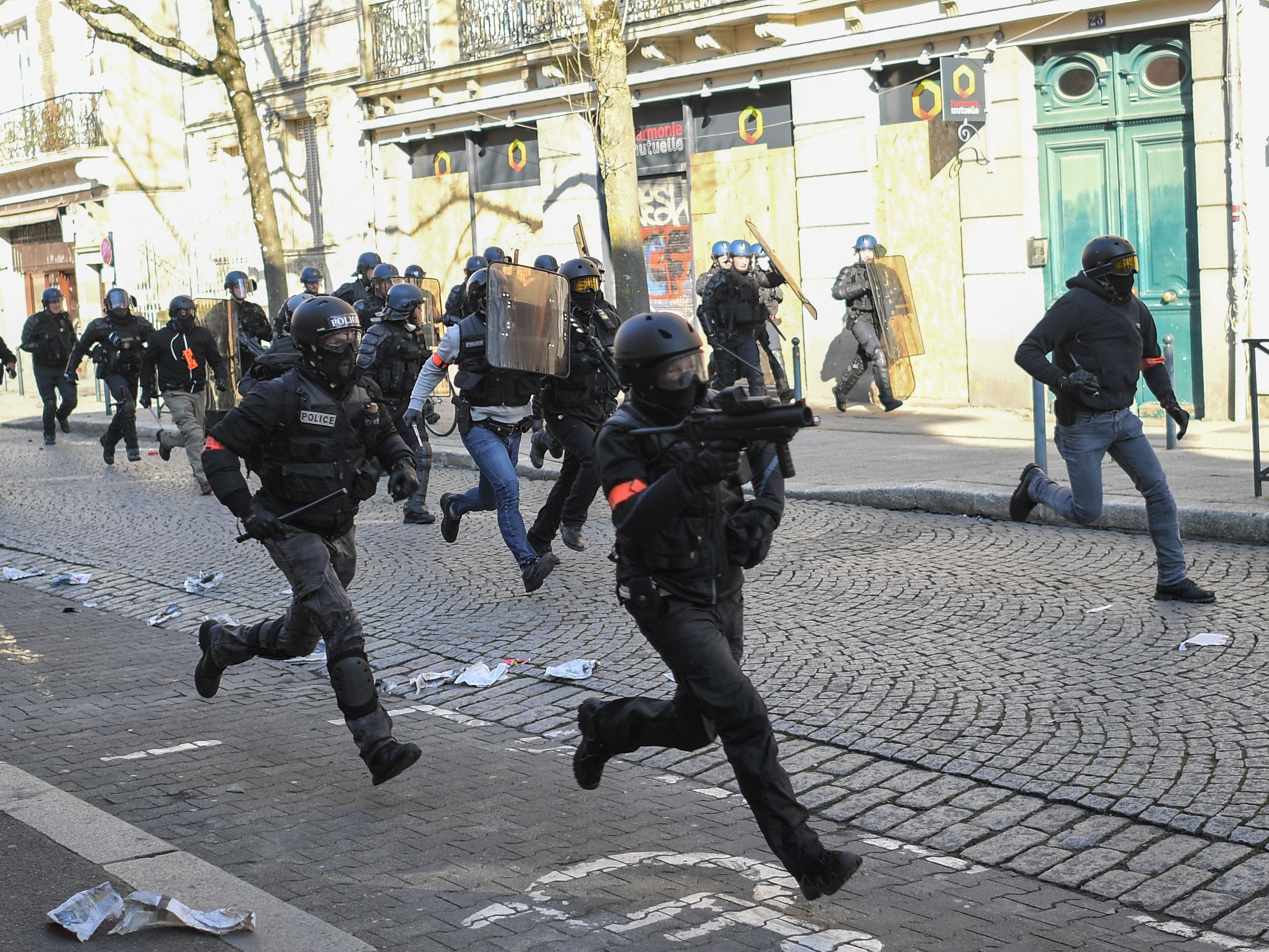 French police run down a street as members of the yellow vest (gilet jaune) take part in the 15th consecutive Saturday of demonstrations in Rennes, western France on February 23, 2019.