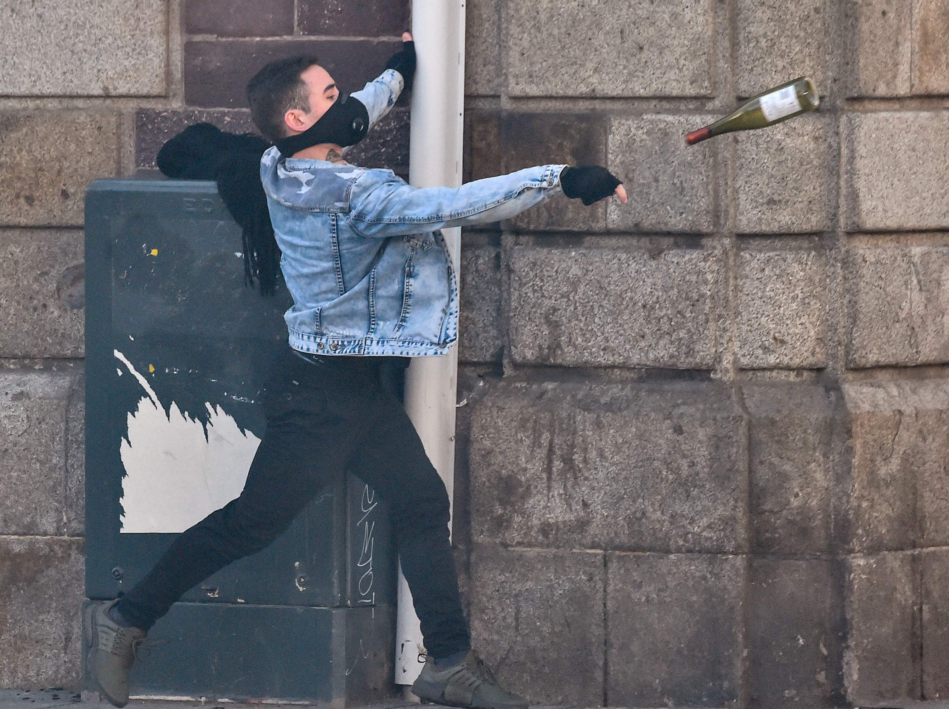 A man lobs a glass bottle as members of the yellow vest (gilet jaune) take part in the 15th consecutive Saturday of demonstrations in Rennes, western France on Feb. 23, 2019.