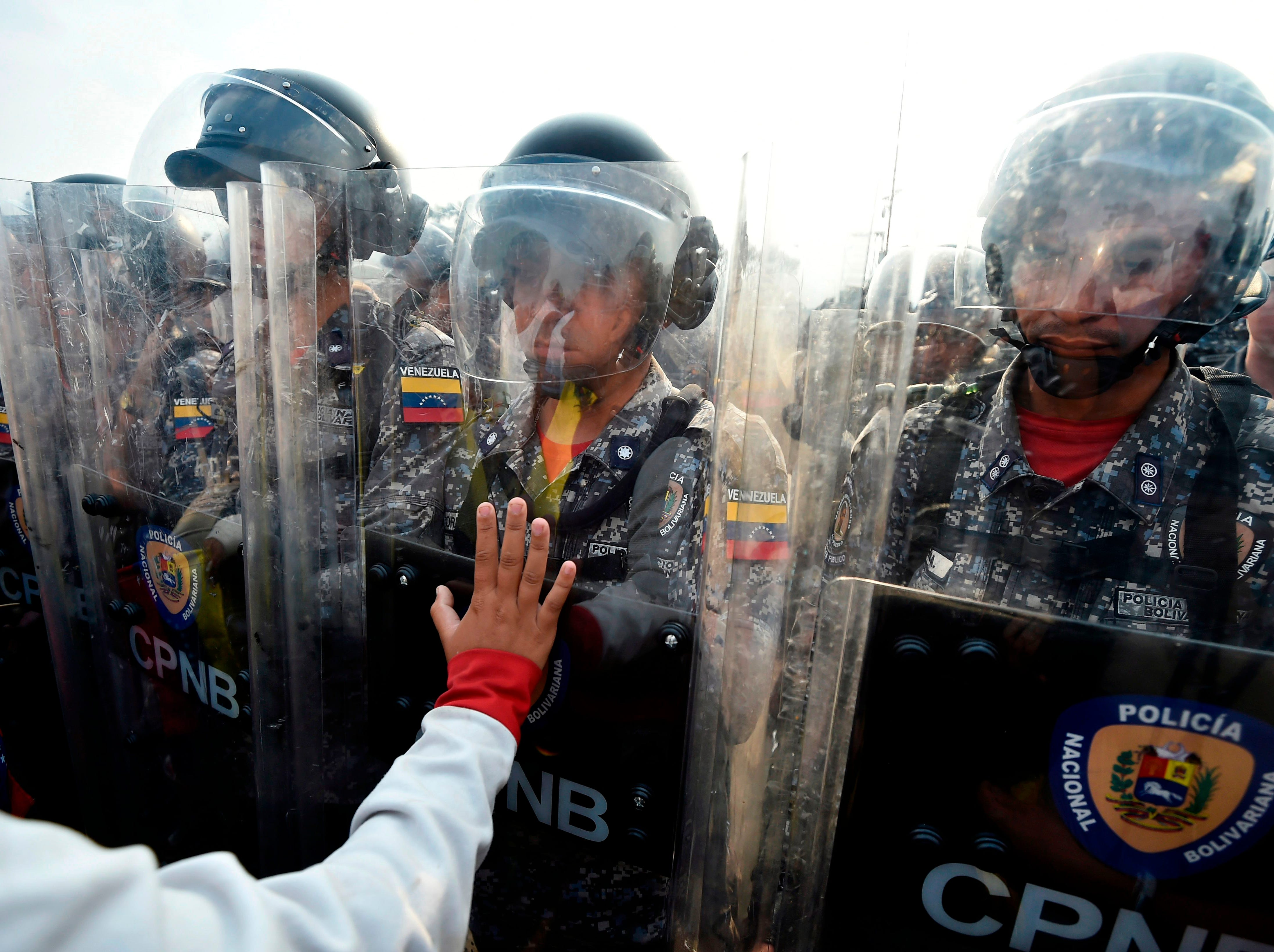 Venezuelans confront national policemen demanding them to let the humanitarian aid in, at the Simon Bolivar bridge, in Cucuta, Colombia after President Nicolas Maduro's government ordered to temporary close down the border with Colombia on Feb. 23, 2019.