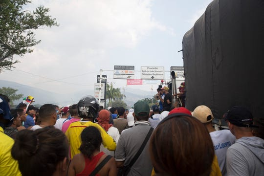 Activists crowd near trucks of food and medicine on Simon Bolivar border crossing on February 23, 2019 as Venezuelan forces send tear gas and rubber bullets at activists.