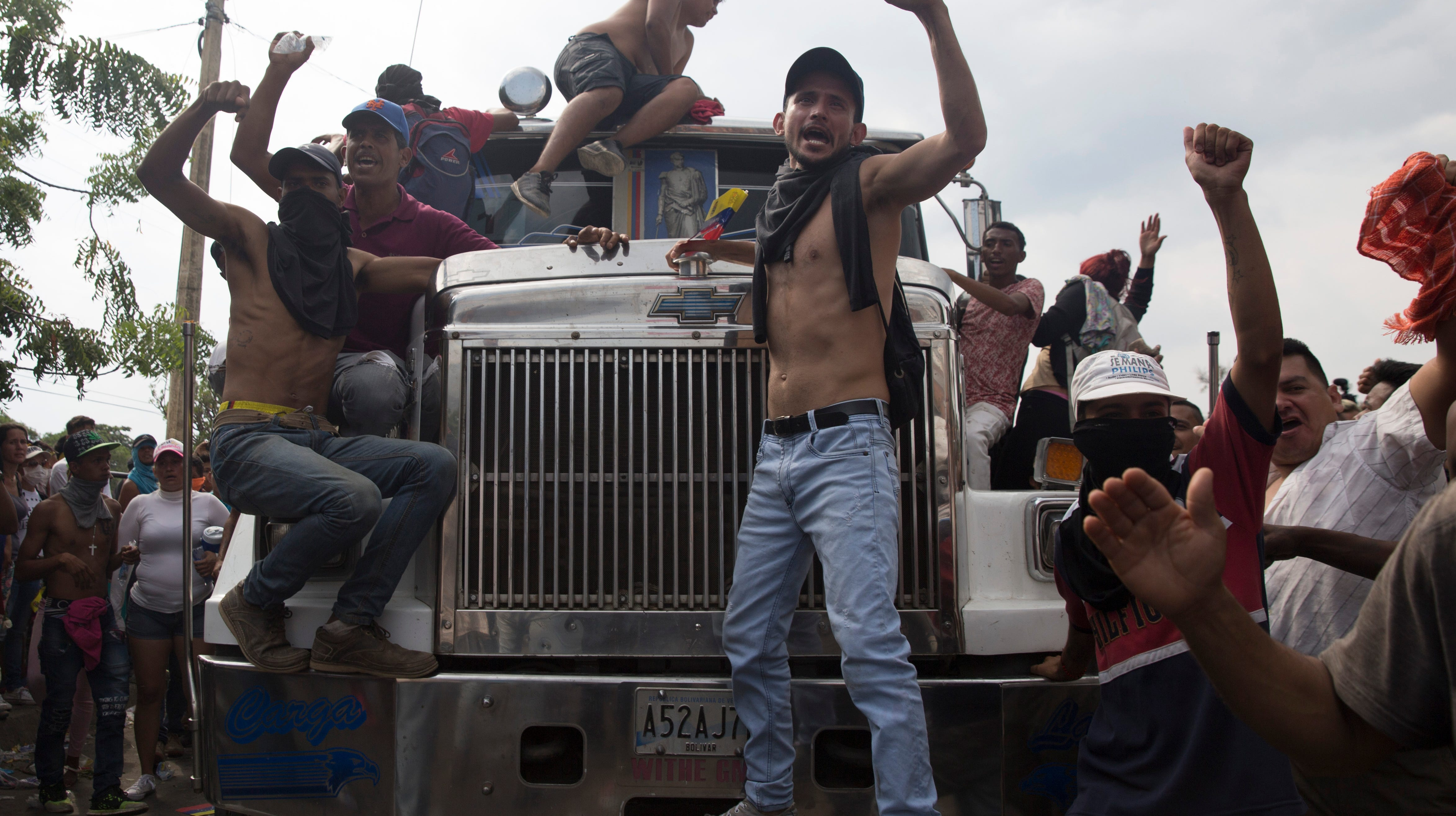 "Activists hang off of trucks loaded up with U.S. humanitarian aid, chanting ""yes we can"" on Simon Bolivar border crossing on February 23, 2019."