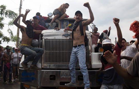 """Activists hang off of trucks loaded up with U.S. humanitarian aid, chanting """"yes we can"""" on Simon Bolivar border crossing on February 23, 2019."""