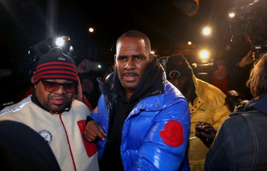 R. Kelly turns himself in at 1st District police headquarters in Chicago on Friday night.