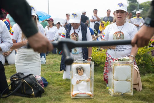 Venezuelans waiting to pass humanitarian aid across the Colombia-Venezuela border pray that there is no violent conflict with President Nicolas Maduro's forces in Cœcuta, Colombia on February 23, 2019.