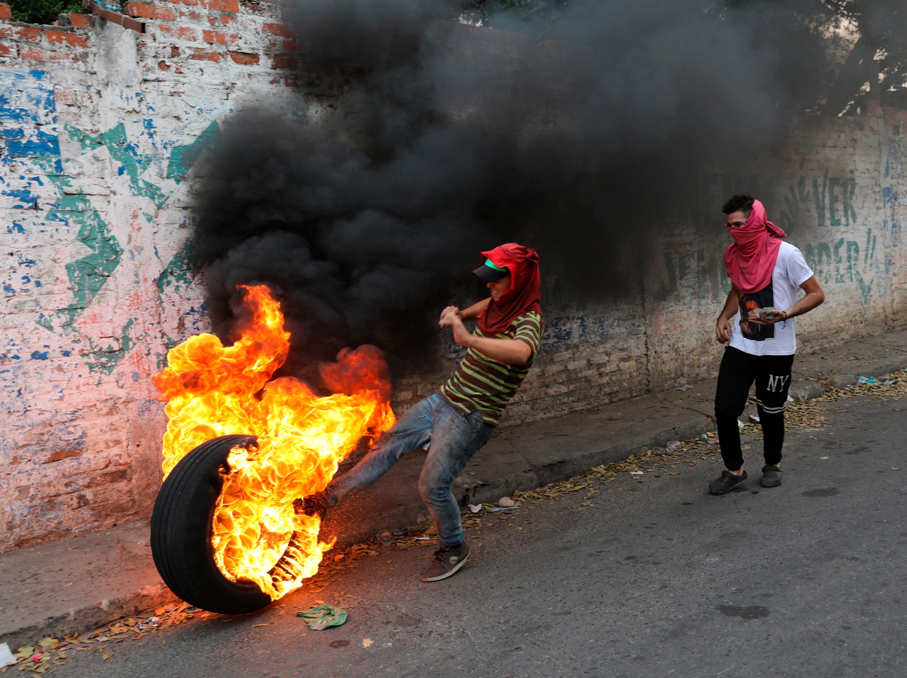 A demonstrator kicks a burning tire during clashes with the police in Urena, Venezuela, near the border with Colombia, Saturday, Feb. 23, 2019. Venezuela's National Guard fired tear gas on residents clearing a barricaded border bridge between Venezuela and Colombia on Saturday, heightening tensions over blocked humanitarian aid that opposition leader Juan Guaido has vowed to bring into the country over objections from President Nicolas Maduro.