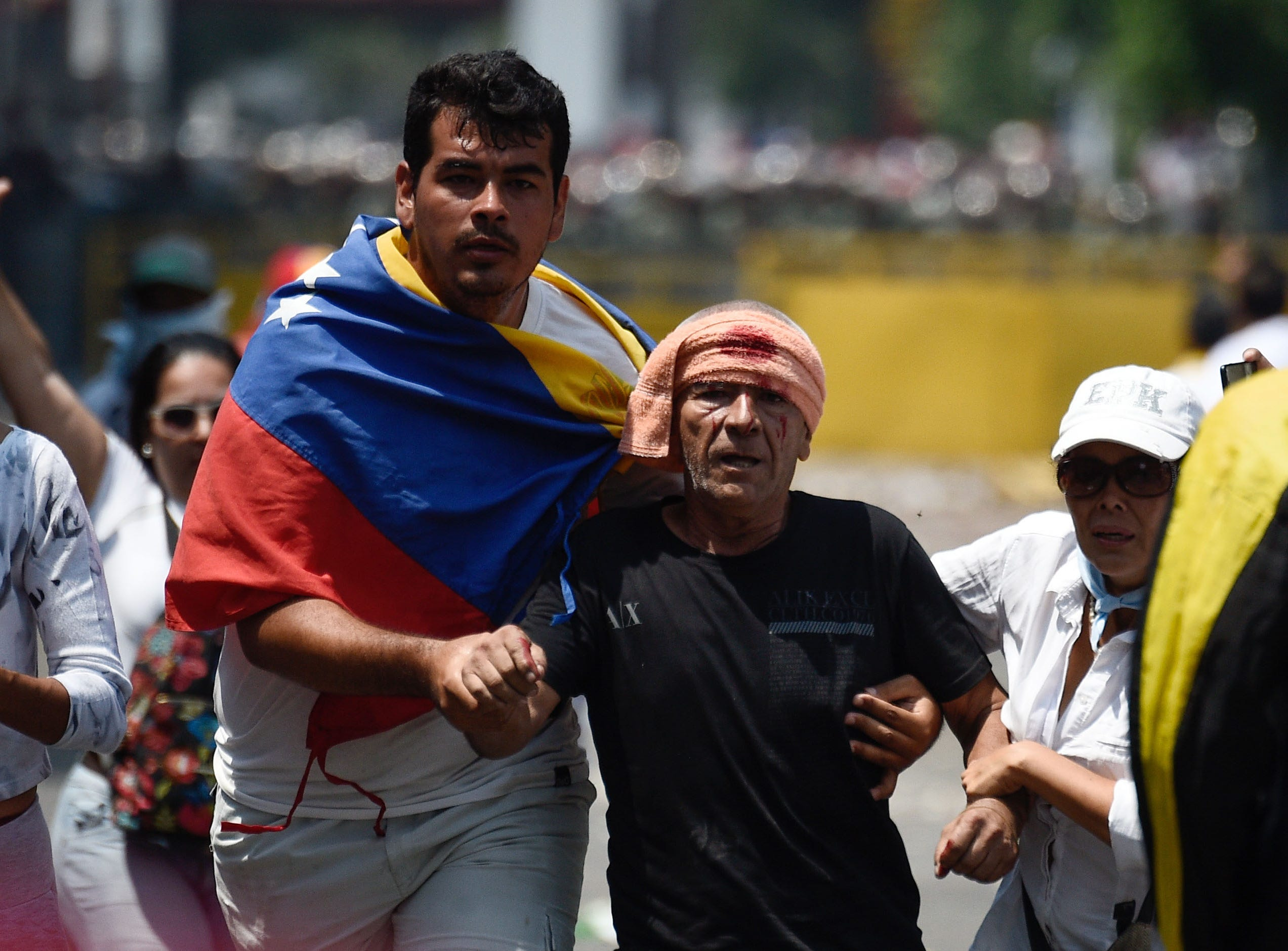 A demonstrator assists an injured protester during an opposition demonstration in San Antonio del Tachira, Venezuela on Feb. 23, 2019.