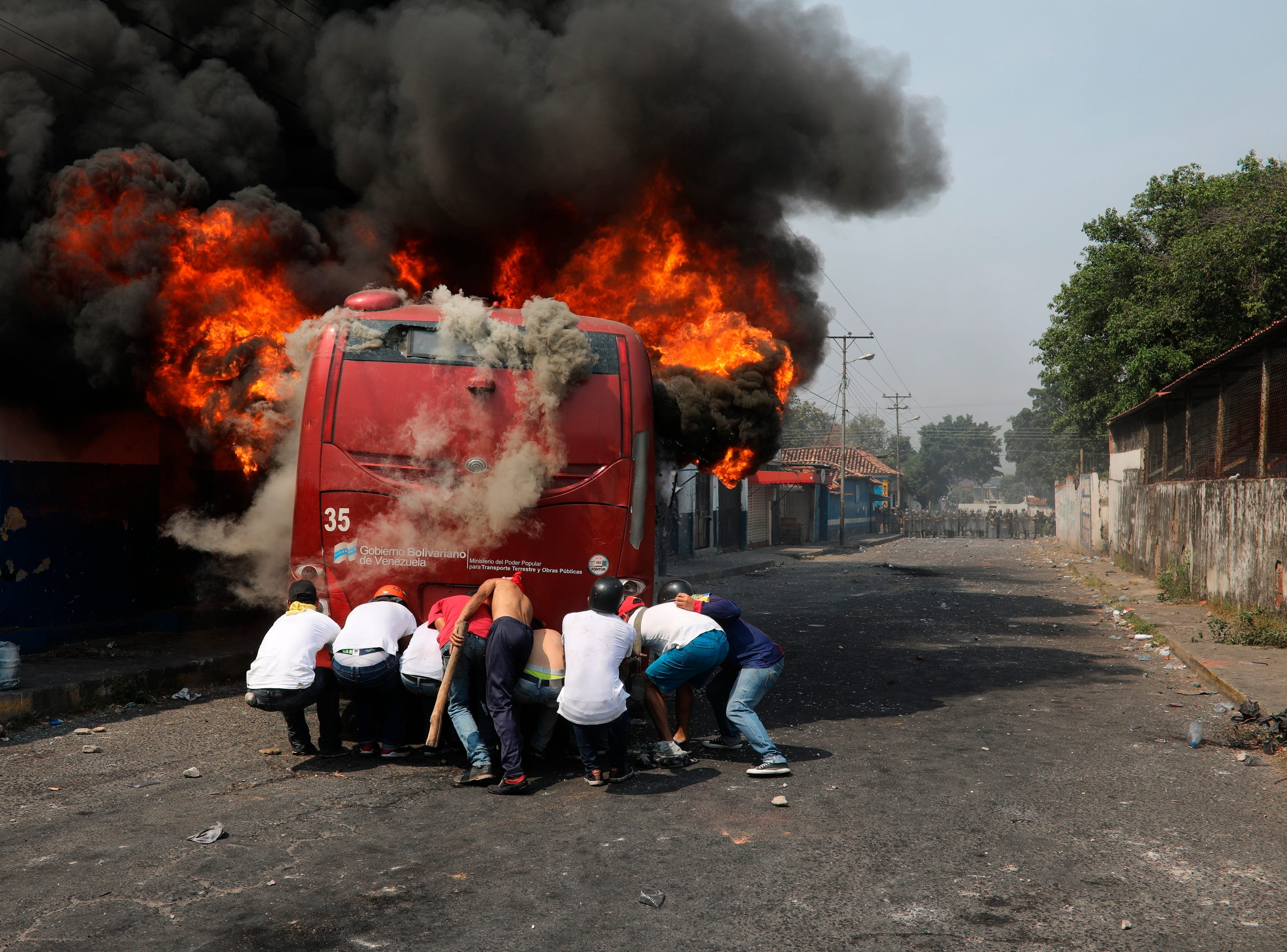 Demonstrators push a bus that was set on fire during clashes with the Bolivarian National Guard in Urena, Venezuela, near the border with Colombia, Saturday, Feb. 23, 2019.