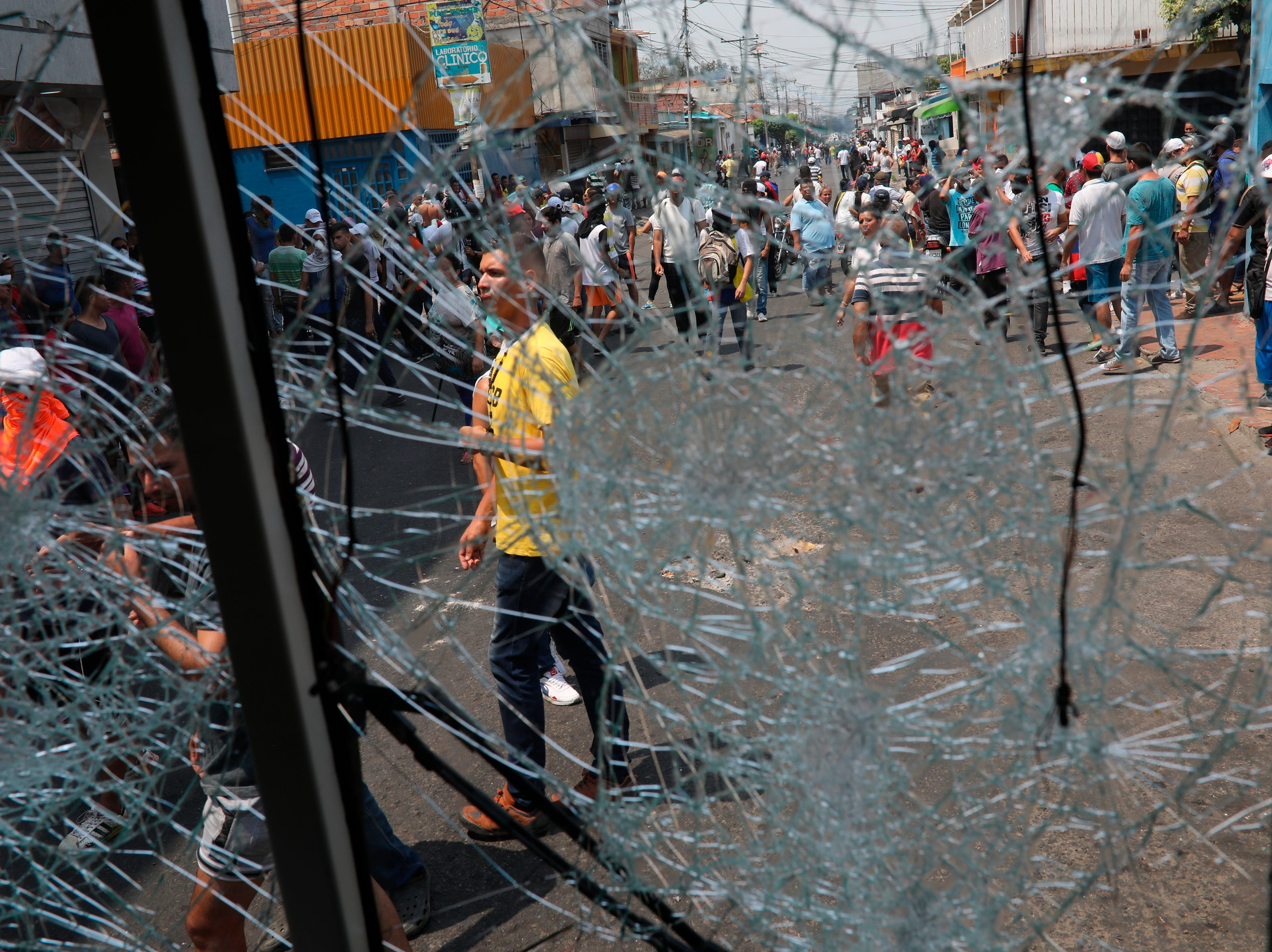 Demonstrators are seen through the cracked windshield of a torched bus during clashes with the Bolivarian National Guard in Urena, Venezuela, near the border with Colombia, Saturday, Feb. 23, 2019.