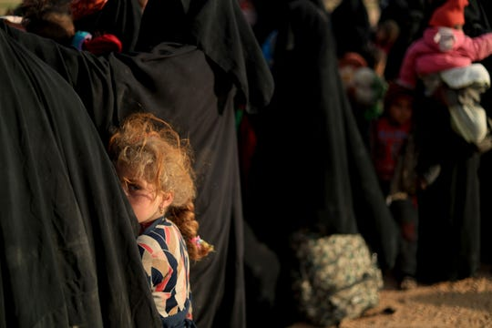 A young girl looks on as women and children who fled the Islamic State group's last embattled holdout of Baghouz wait to evacuate the area in Syria's northern Deir Ezzor province, on Feb. 22, 2019.
