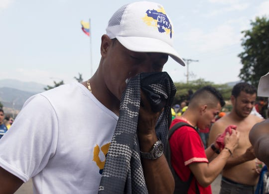 An activist trying to pass U.S. humanitarian aid into Venezuela wipes tears from his eyes after being tear gassed by Venezuelan forces on the Simon Bolivar border crossing on February 23, 2019.