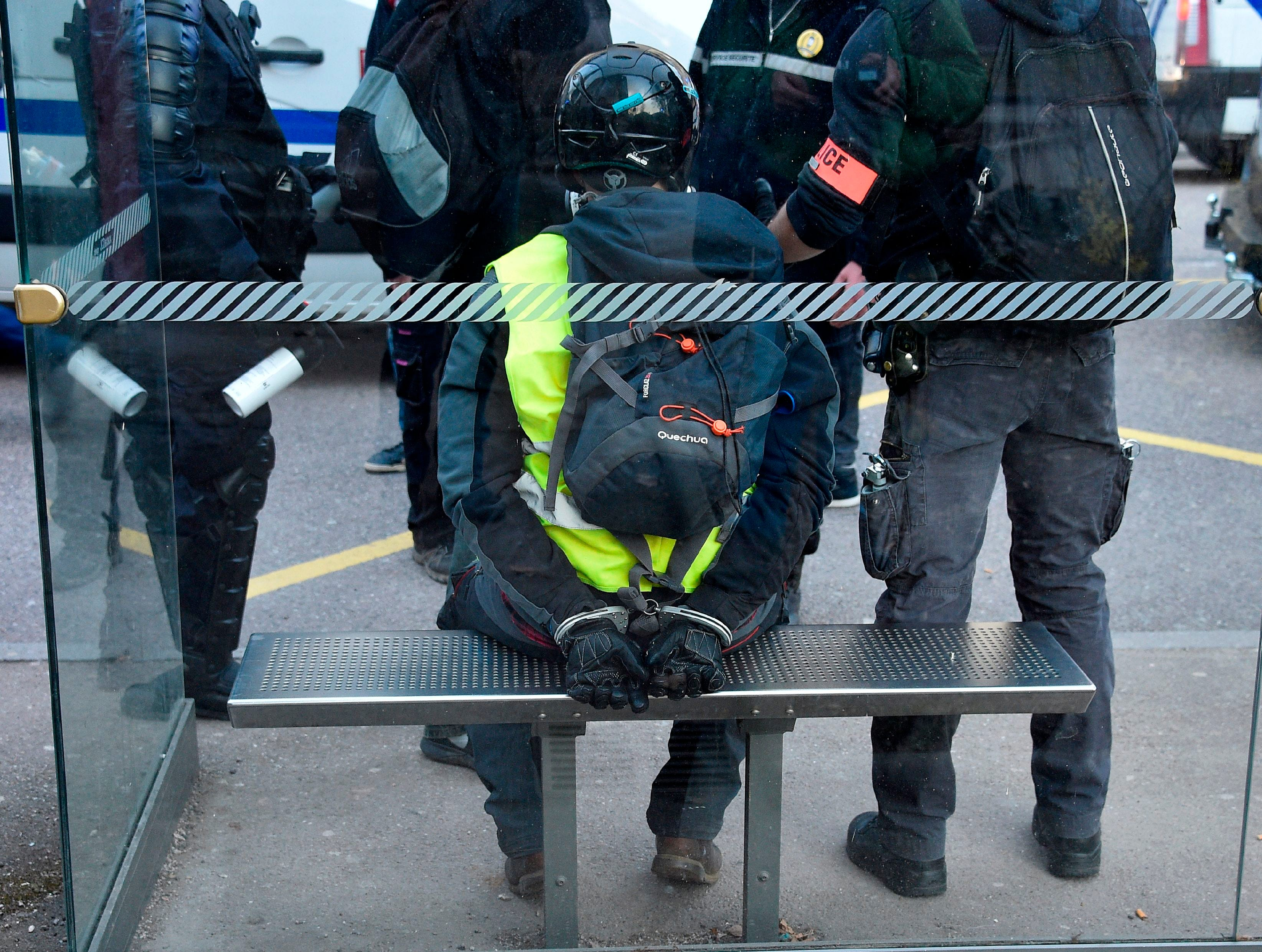 "A handcuffed yellow vest protesters is surrounded by police during a ""yellow vest"" (gilets jaunes) anti-government demonstration in Epinal, eastern France, on February 23, 2019.  Demonstrators took to the streets in France for a 15th consecutive week of nationwide protest against the French President's policies and his top-down style of governing, high cost of living, government tax reforms and for more ""social and economic justice."""