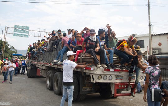 Venezuelans sit on trucks loaded with mostly U.S. humanitarian aid on the Simon Bolivar border crossing and Venezuelan military tear gas activists yards away on February 23, 2019.