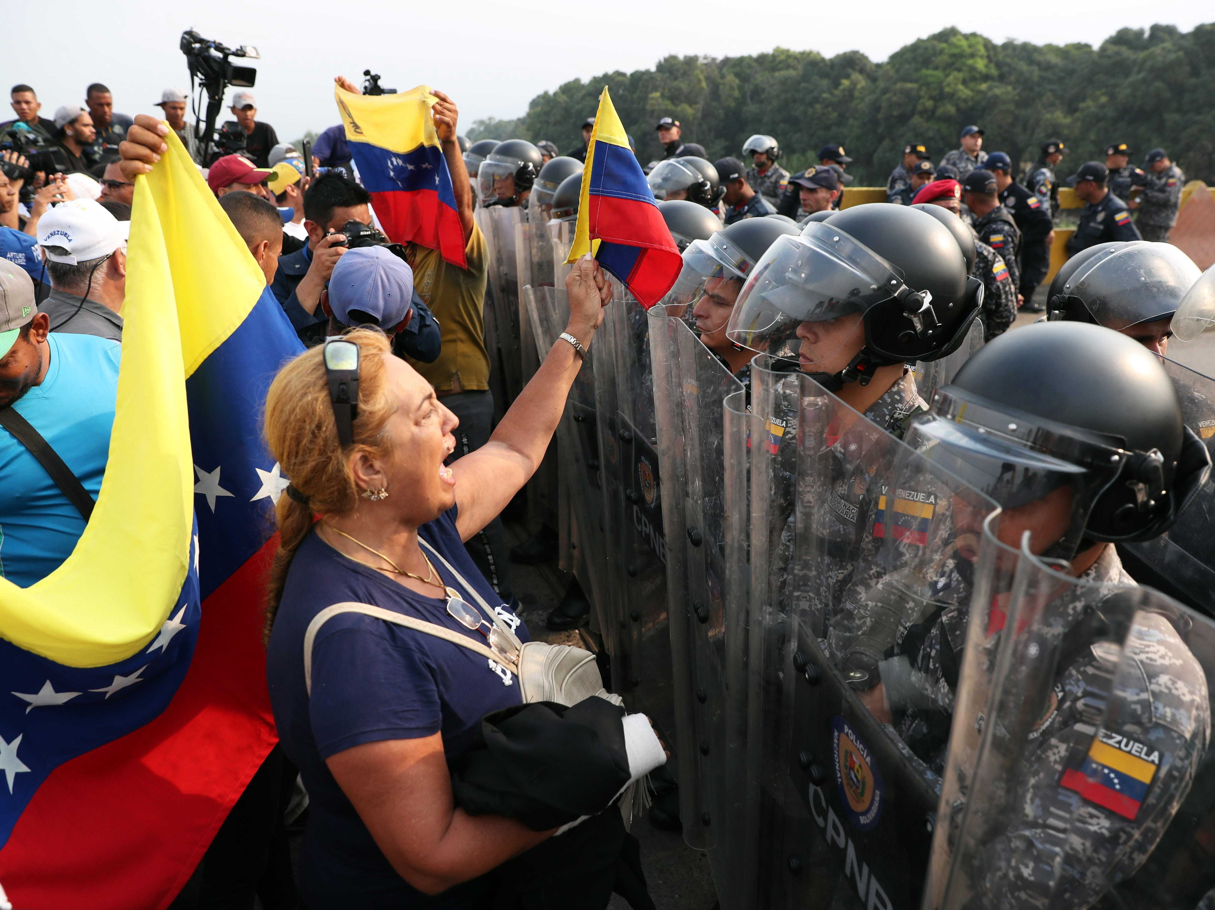 Venezuelans stand in front of Venezuelan Army forces members at the Simon Bolivar bridge on the border with Venezuela, in Cucuta, Colombia on Feb. 23, 2019. In the Colombia-Venezuela frontier bridges, hundreds of people are expecting for the crossing of the Humanitarian Aid, as it has been announced by the Parliament President Juan Guaido .