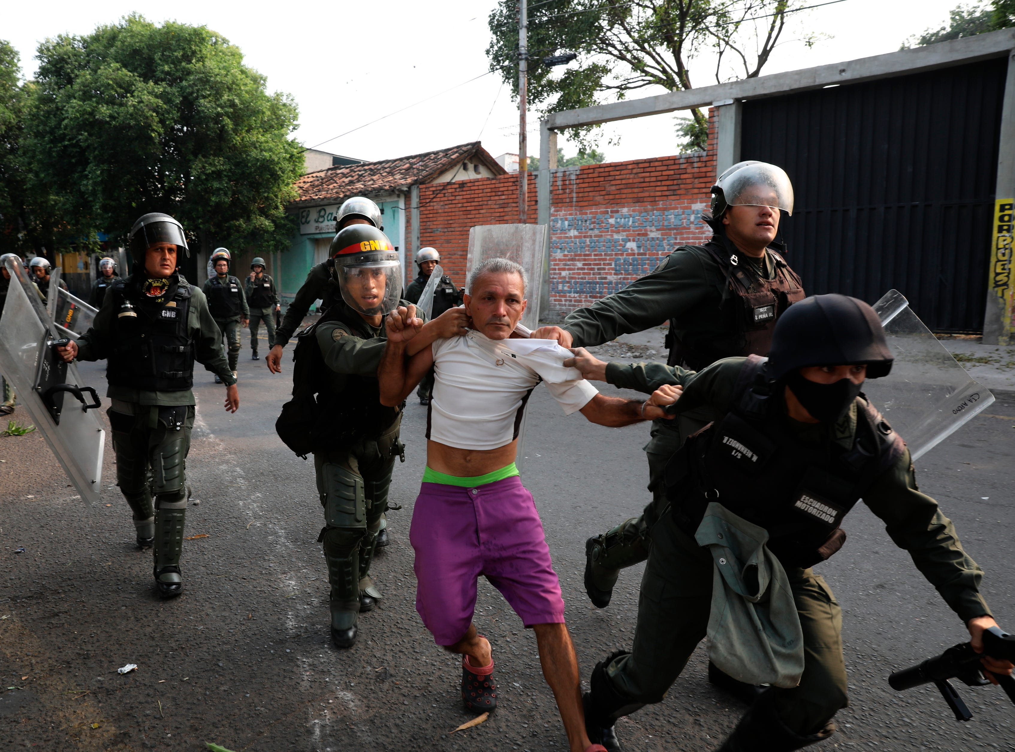 A man is detained during clashes with the Bolivarian National Guard in Urena, Venezuela, near the border with Colombia, Saturday, Feb. 23, 2019.