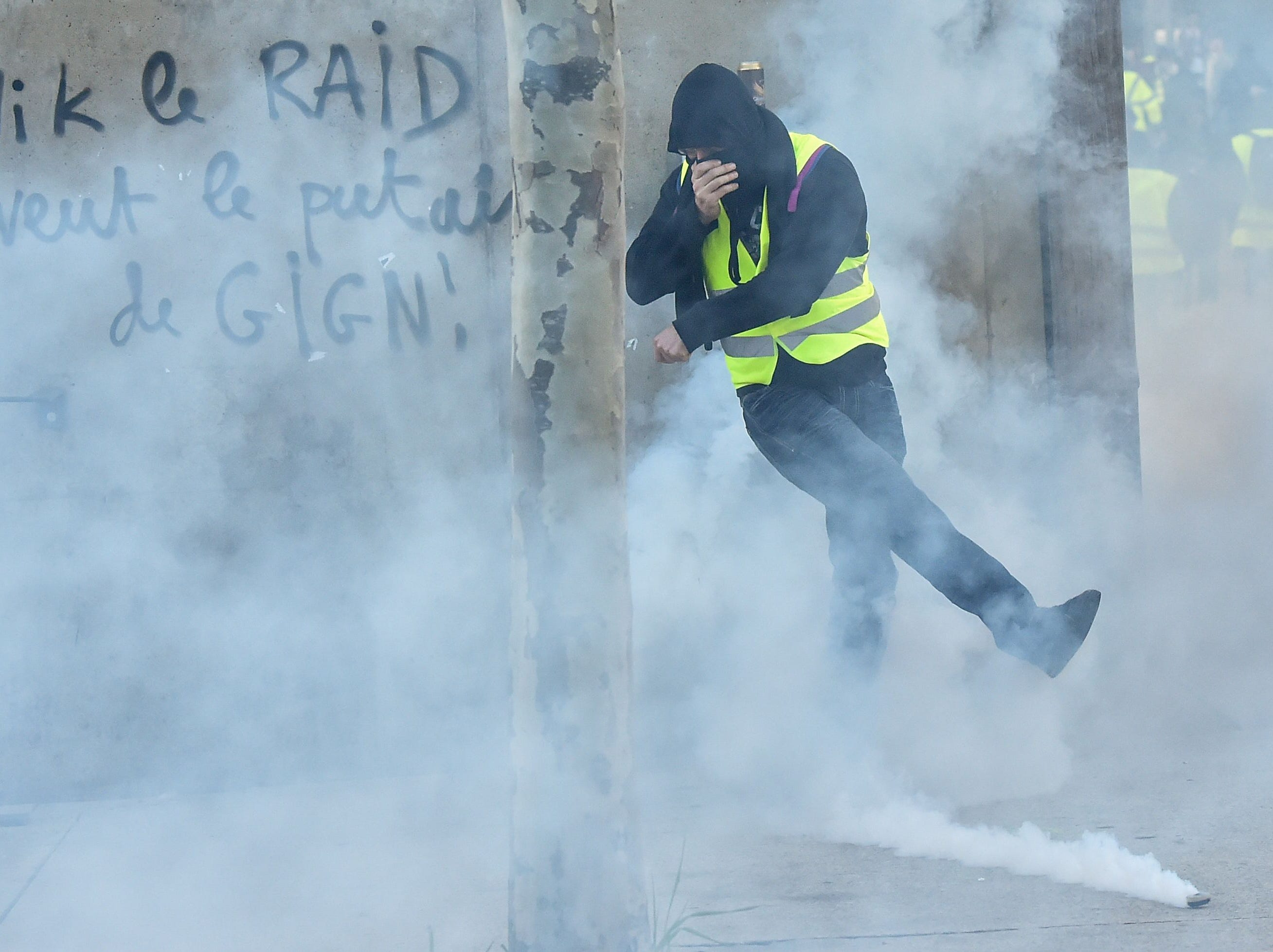 A member of the yellow vest (gilet jaune) kicks away a tear gas canister as he takes part in the 15th consecutive Saturday of demonstrations in Rennes, western France on Feb. 23, 2019.