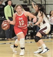 Hermleigh's Sandra Carr (12) dribbles around a Rankin defender in the Region II-1A championship game last weekend at ACU's Moody Coliseum. The Lady Cardinals return to the state tournament, playing Nazareth on Thursday morning in San Antonio.