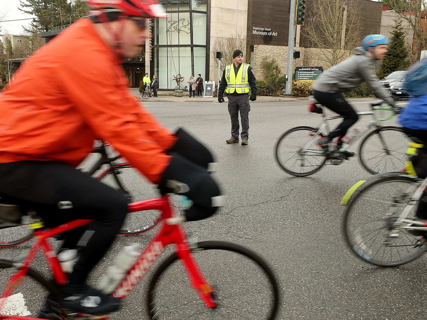 Bainbridge Island Police Detective Eric Peffer directs traffic and cyclists at the ferry intersection and Winslow Way during Cascade Bicycle Club's annual Chilly Hilly ride around Bainbridge Island on Sunday, February 24, 2019.