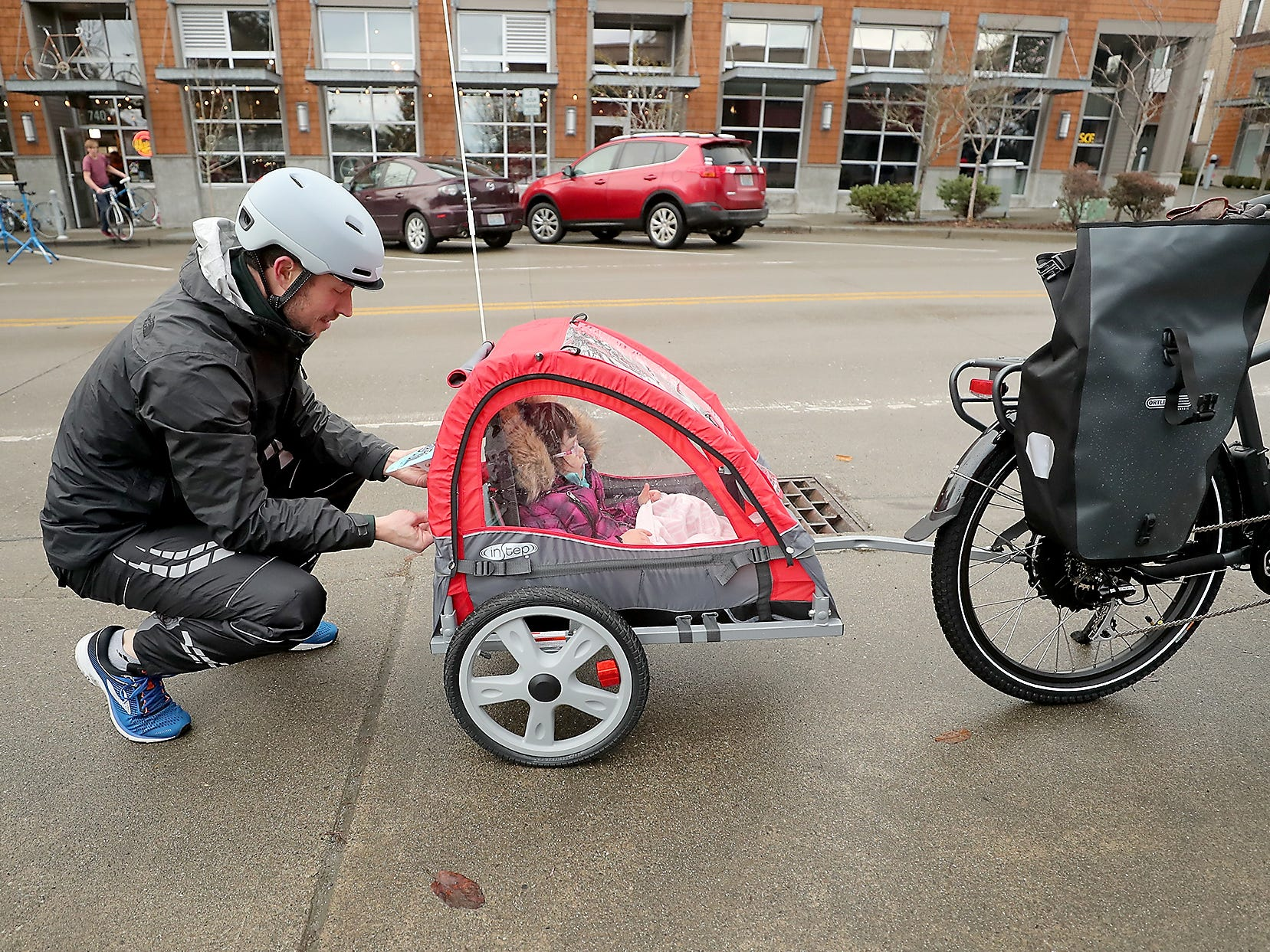 Jonathan Burr, of Bainbridge Island, grabs a pair of gloves out of the trunk for daughter Harper, 3, as they begin Cascade Bicycle Club's annual Chilly Hilly ride around Bainbridge Island on Sunday, February 24, 2019.