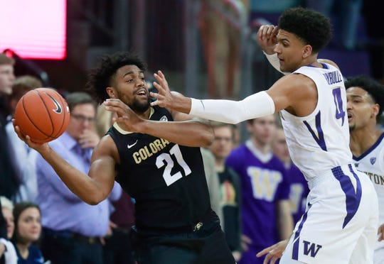 Colorado forward Evan Battey (21) passes around the defense of Washington guard Matisse Thybulle (4) during the first half of an NCAA college basketball game Saturday, Feb. 23, 2019, in Seattle. (AP Photo/Ted S. Warren)