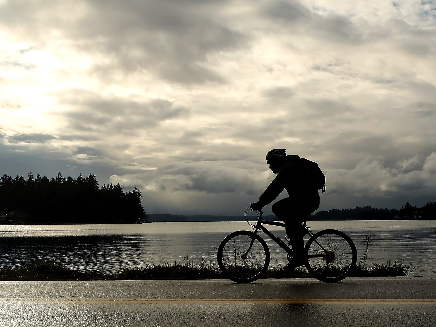 A cyclists is silhouetted against the clouds as the pedal along Point White Drive during Cascade Bicycle Club's annual Chilly Hilly ride around Bainbridge Island on Sunday, February 24, 2019.