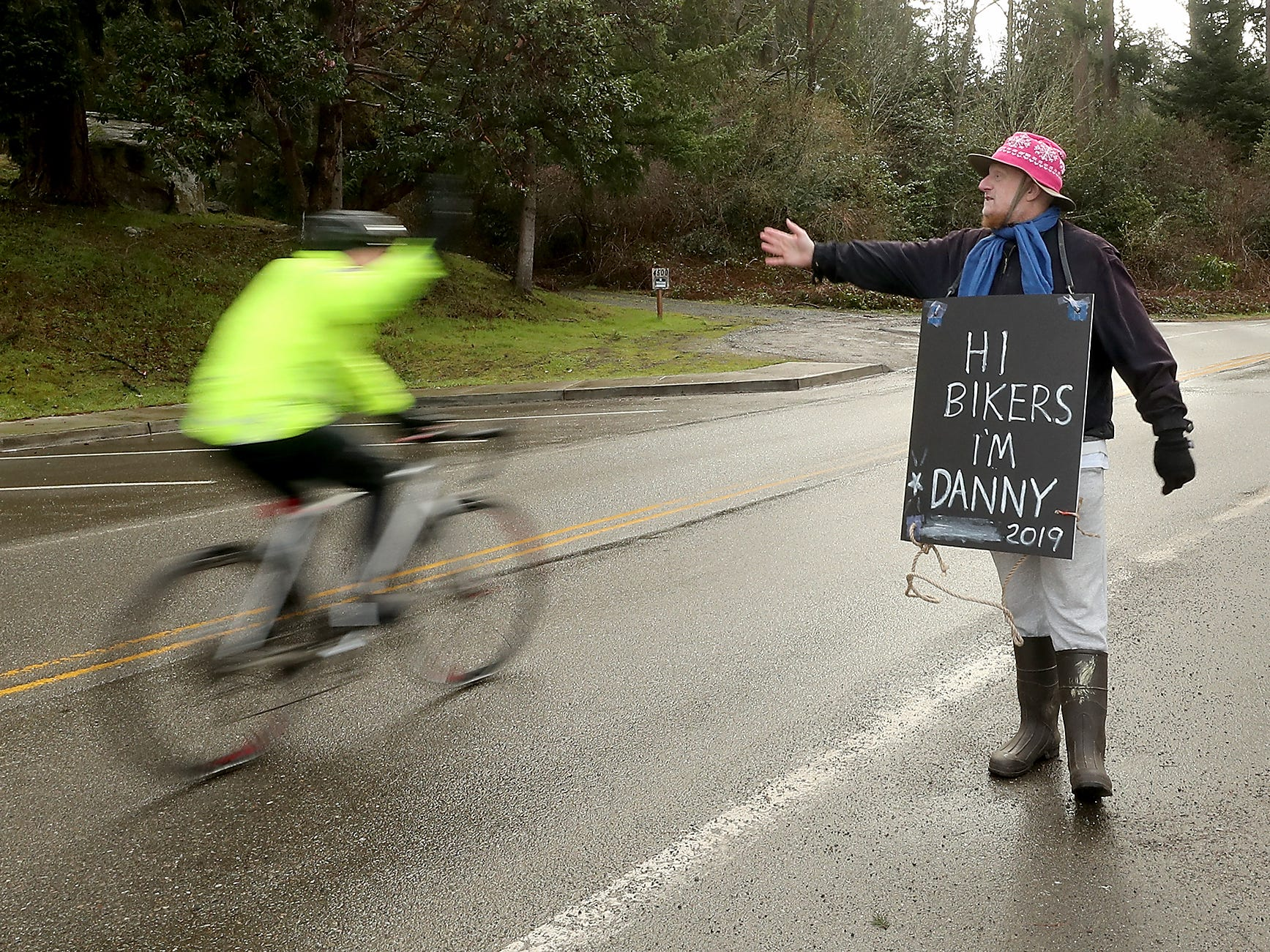 Danny Hadden waves and waves and offers high fives to cyclists as the pass by him in Lynwood Center during Cascade Bicycle Club's annual Chilly Hilly ride around Bainbridge Island on Sunday, February 24, 2019.