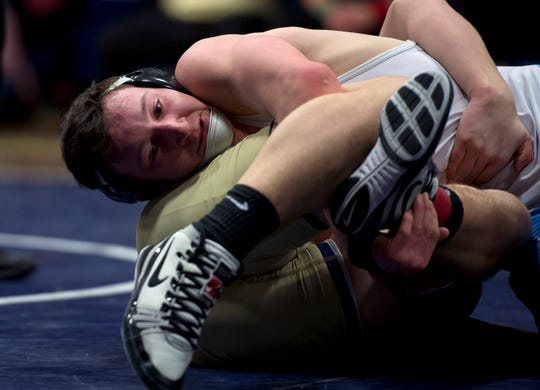 Mount Mansfield's Colby Giroux works against Essex's Seth Carney in the 170-pound final at the 2019 Vermont high school wrestling state championships on Saturday at Essex High School.