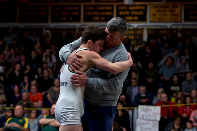 St. Johnsbury coach Mike Verge, right, hugs his son Hunter after winning the 120-pound final at the 2019 Vermont high school wrestling state championships on Saturday at Essex High School.