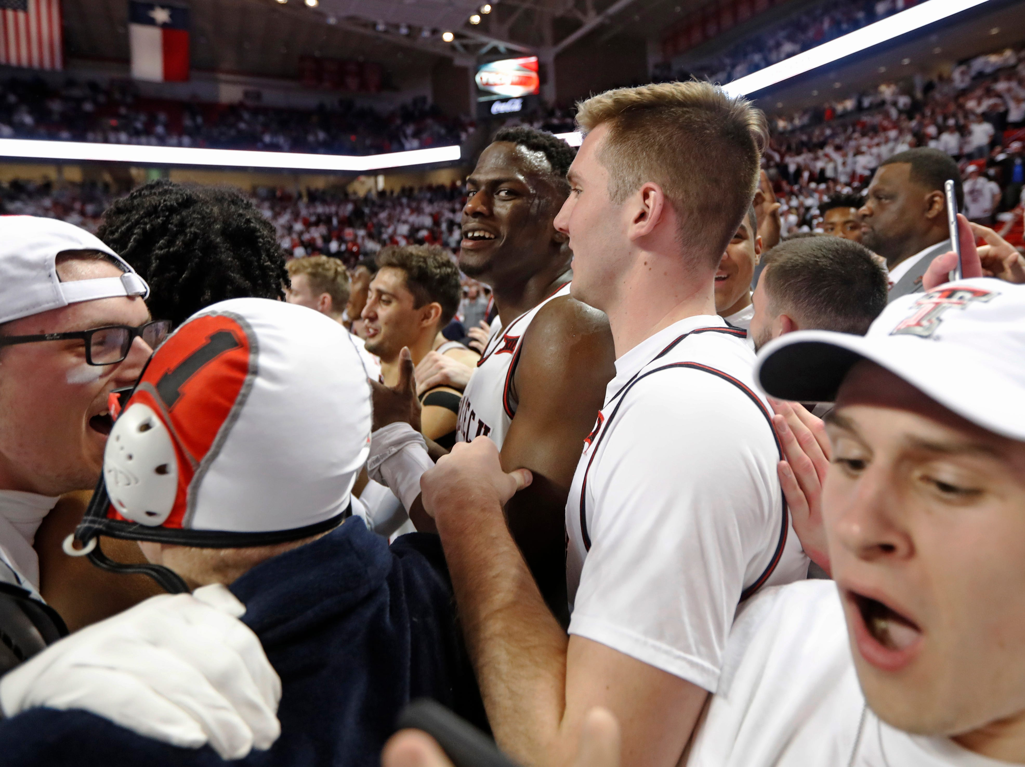 Texas Tech's Norense Odiase (32) and Andrew Sorrells (30) are surrounded by fans running onto the court after an NCAA college basketball game against Kansas, Saturday, Feb. 23, 2019, in Lubbock, Texas. Texas Tech won 91-62 (AP Photo/Brad Tollefson)