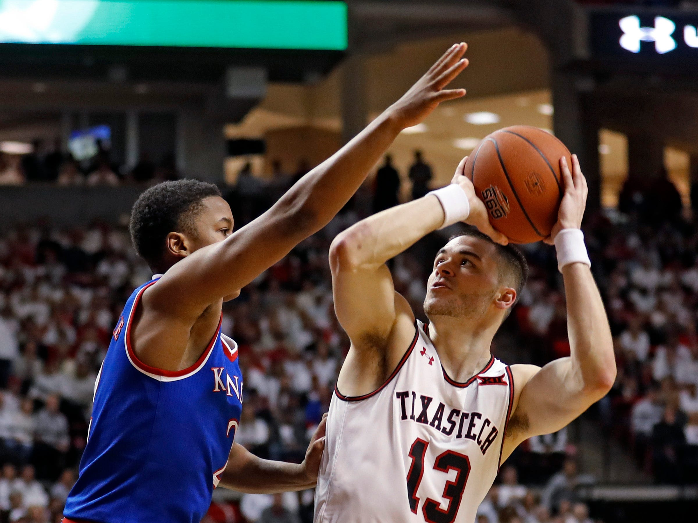 Texas Tech's Matt Mooney (13) looks for a shot over Kansas' Charlie Moore (2) during the first half of an NCAA college basketball game Saturday, Feb. 23, 2019, in Lubbock, Texas. (AP Photo/Brad Tollefson)