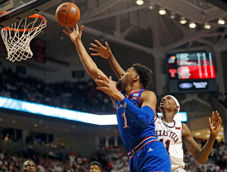 Kansas' Dedric Lawson (1) shoots next to Texas Tech's Tariq Owens (11) during the first half of an NCAA college basketball game Saturday, Feb. 23, 2019, in Lubbock, Texas. (AP Photo/Brad Tollefson)
