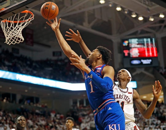 Kansas' Dedric Lawson (1) shoots next to Texas Tech's Tariq Owens (11) during the first half of an NCAA college basketball game Saturday, Feb. 23, 2019, in Lubbock, Texas. (AP Photo/Brad Tollefson)
