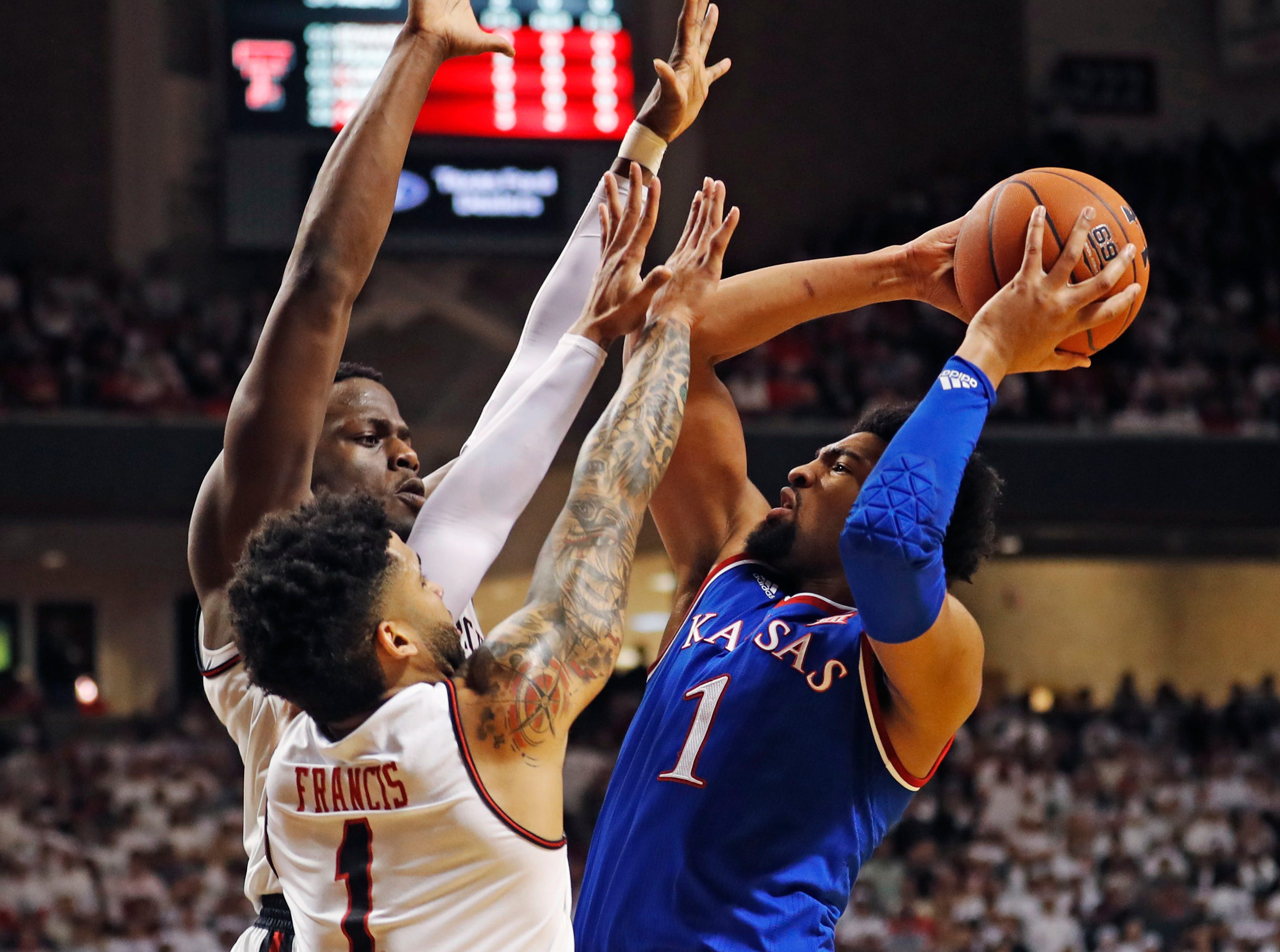 Kansas' Dedric Lawson (1) tries to shoot over Texas Tech's Norense Odiase and Brandon Francis (1) during the first half of an NCAA college basketball game Saturday, Feb. 23, 2019, in Lubbock, Texas. (AP Photo/Brad Tollefson)