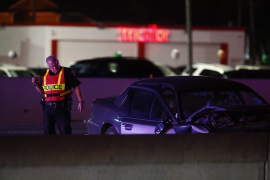 A Corpus Christi police officer looks over a wrecked car on SPID on Saturday, Feb. 23, 2019 after a major accident shut down the highway.
