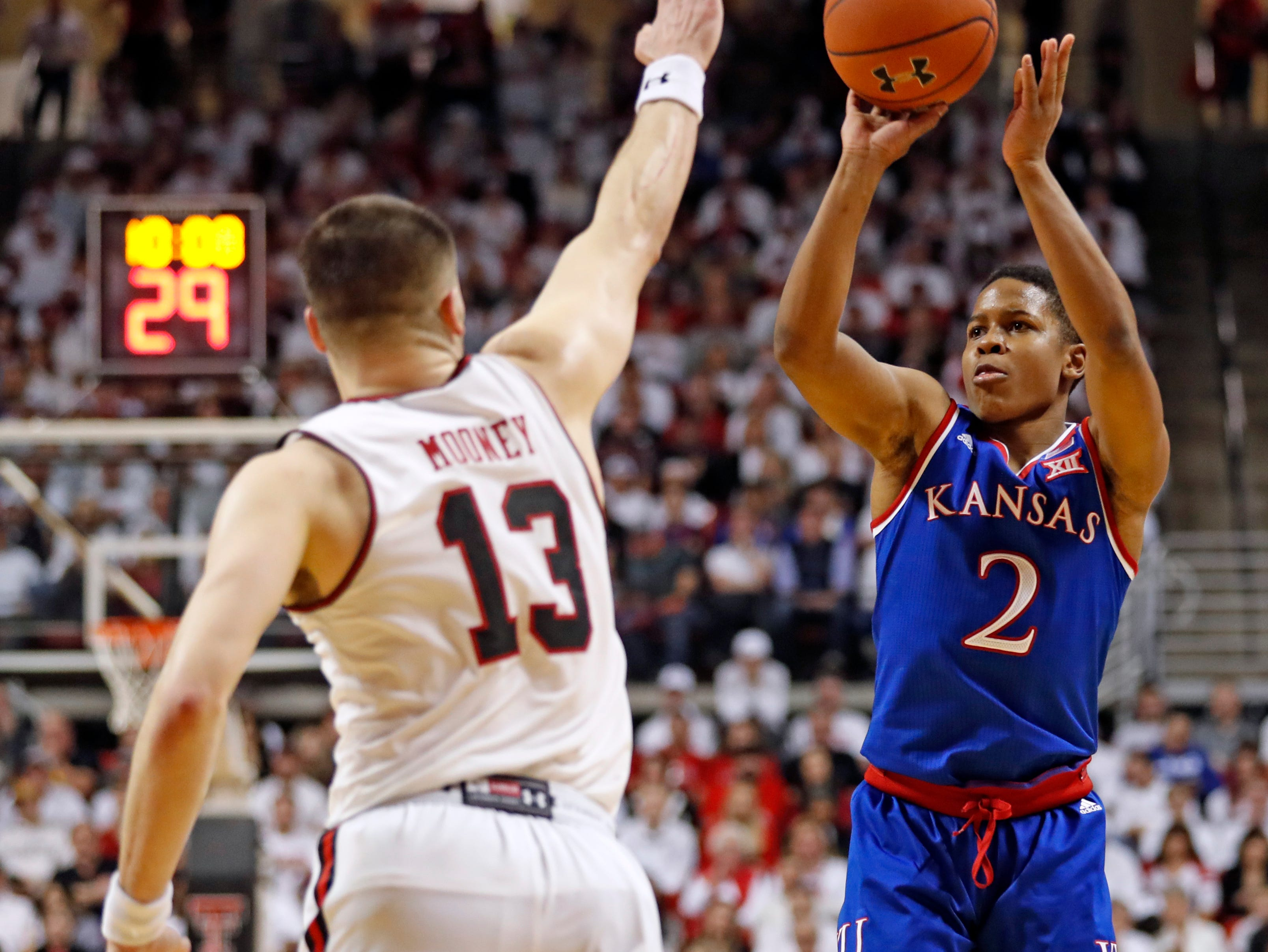 Kansas' Charlie Moore (2) shoots over Texas Tech's Matt Mooney (13) during the second half of an NCAA college basketball game Saturday, Feb. 23, 2019, in Lubbock, Texas. (AP Photo/Brad Tollefson)