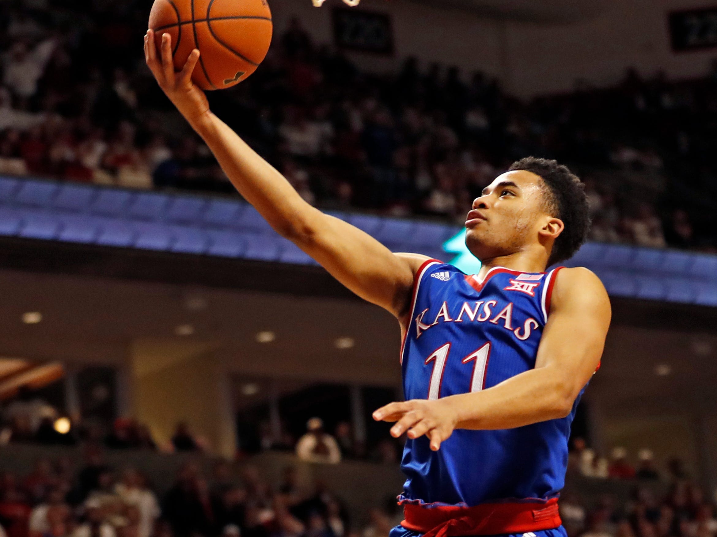 Kansas' Devon Dotson (11) lays up the ball during the first half of the team's NCAA college basketball game against Texas Tech on Saturday, Feb. 23, 2019, in Lubbock, Texas. (AP Photo/Brad Tollefson)