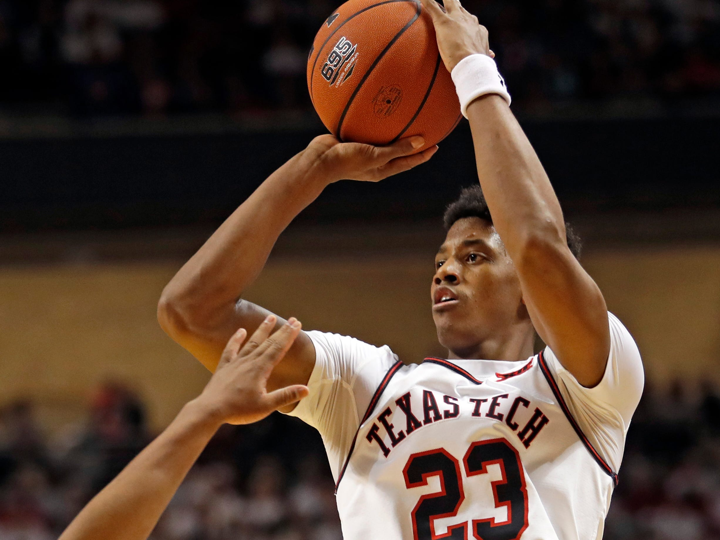 Texas Tech's Jarrett Culver (23) shoots over Kansas' Charlie Moore (2) during the first half of an NCAA college basketball game Saturday, Feb. 23, 2019, in Lubbock, Texas. (AP Photo/Brad Tollefson)