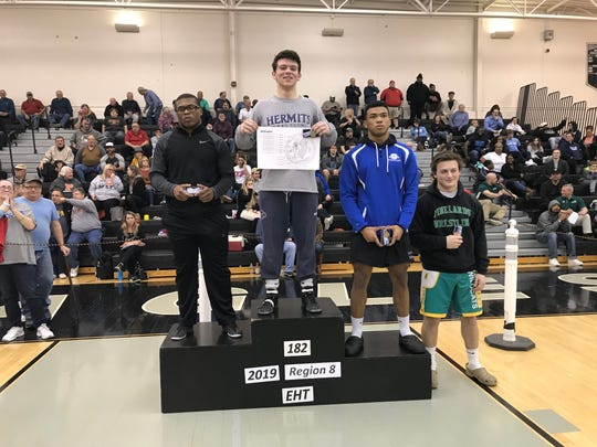 St. Augustine's Mike Misita stands on top of the podium after winning the 182-pound championship at the Region 8 Tournament on Saturday at Egg Harbor Township.