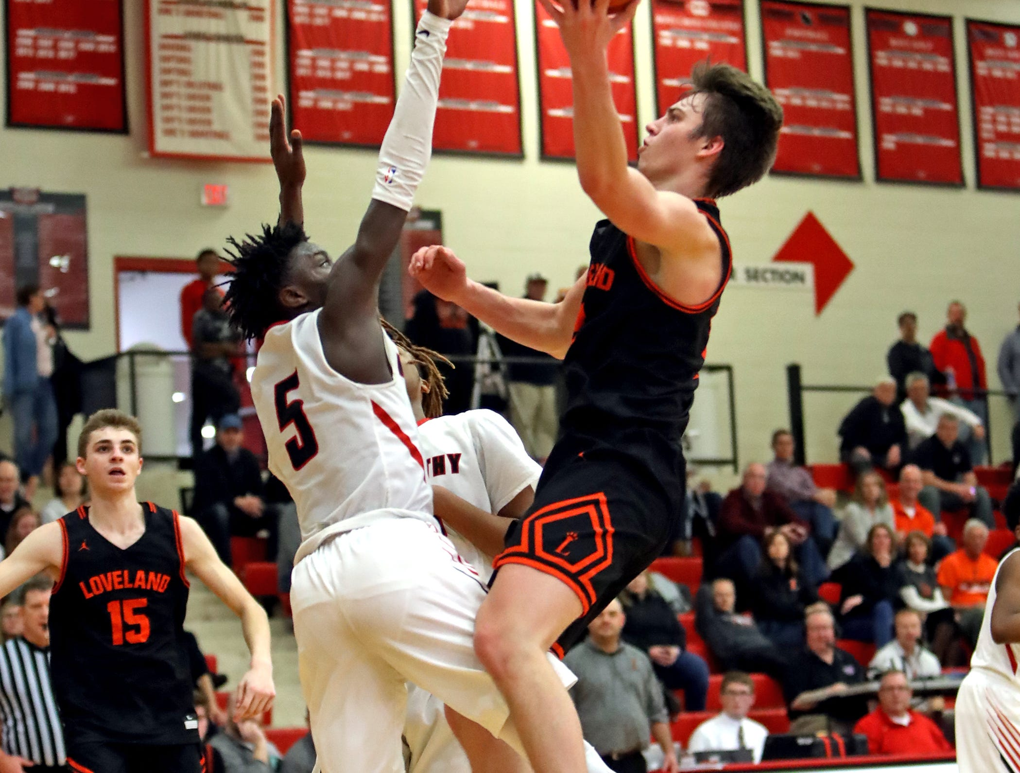 Loveland guard Jalen Greiser drives through the heart of the Owls defense and scores in the sectional playoffs at Lakota West High School Feb. 23, 2019. Mount Healthy defeated Loveland 62-57.
