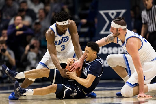 Xavier Musketeers guard Quentin Goodin (3) and Xavier Musketeers forward Zach Hankins (35) wrap up Villanova Wildcats guard Jahvon Quinerly (1) in the first half of the NCAA men's basketball game between Xavier Musketeers and Villanova Wildcats on Saturday, Feb. 24, 2019, at Cintas Center in Cincinnati.