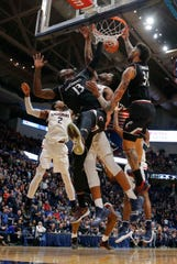 Cincinnati Bearcats forward Tre Scott (13) and guard Jarron Cumberland (34) work for the loose ball against Connecticut Huskies forward Josh Carlton (25) and guard Tarin Smith (2) in the second half at XL Center. Cincinnati defeated UConn 64-60.