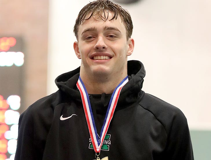 Mason swimmer Adam Chaney stands on the podium after winning the boys 50 free at the OHSAA state swimming and diving championships in Canton, Ohio, Friday, Feb. 23, 2019.