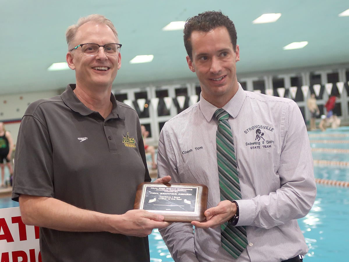 Sycamore head Dan Carl (left) receives the boys coach of the year award at the OHSAA state swimming and diving championships in Canton, Ohio, Friday, Feb. 23, 2019.