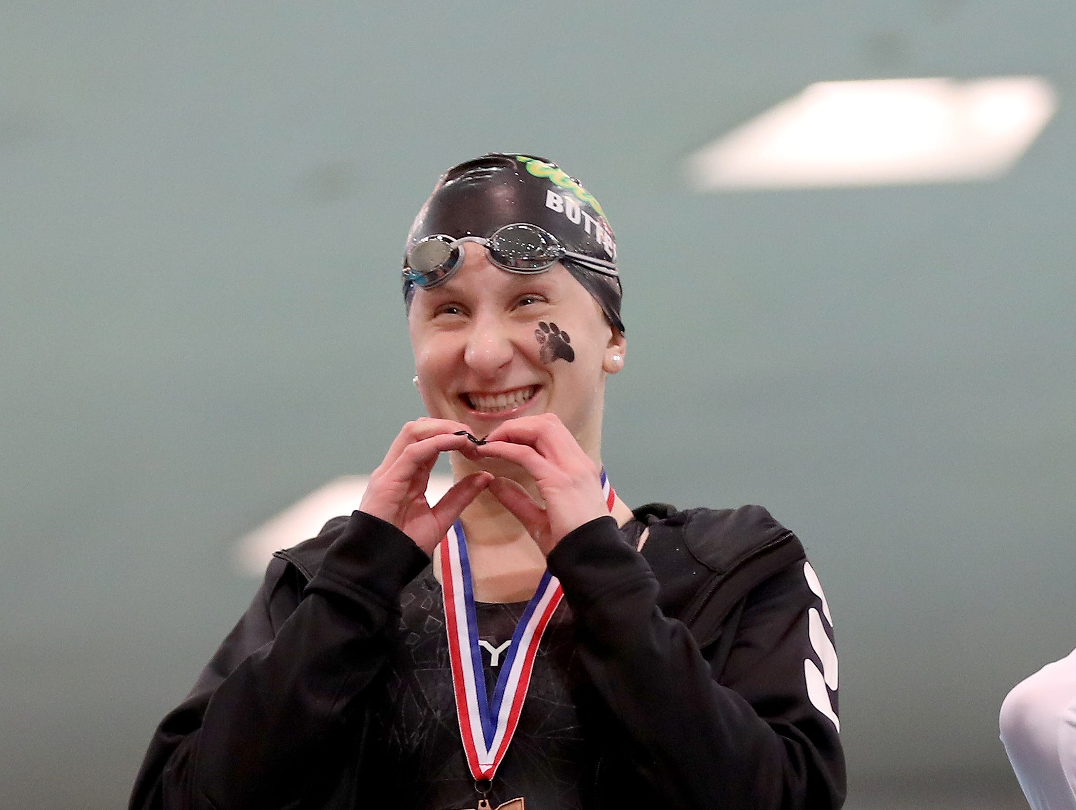 Ursuline swimmer Claudia Butterfield celebrates on the podium at the OHSAA state swimming and diving championships in Canton, Ohio, Friday, Feb. 23, 2019.