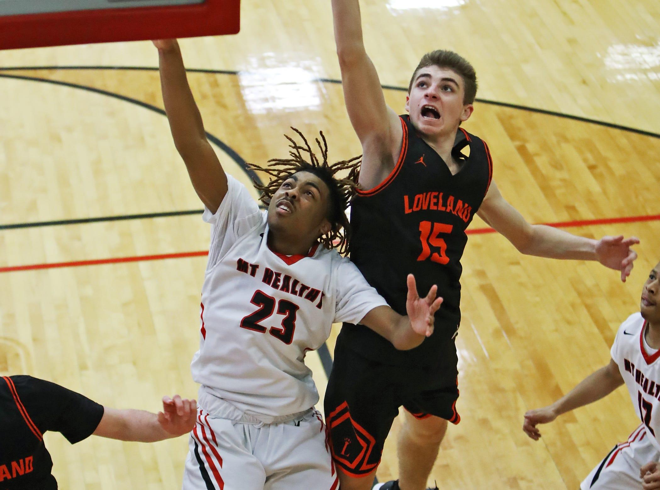 Loveland guard Matt Toigo and Mount Healthy guard Chris Simmons battle for a rebound in the sectional playoffs at Lakota West High School Feb. 23, 2019. Mount Healthy defeated Loveland 62-57.