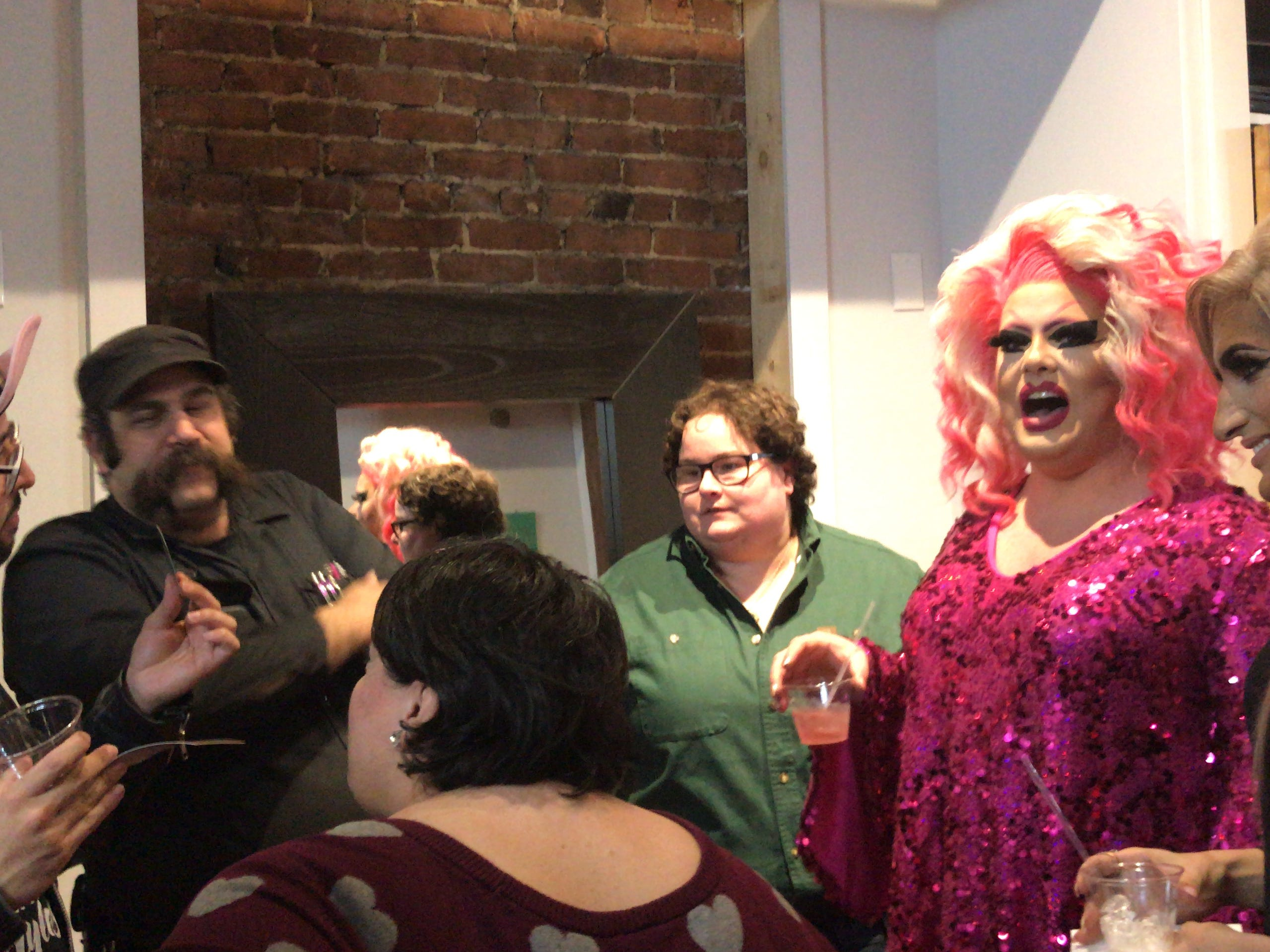 Artist David Ayllon, far left, chats with husband, Pissi Myles, second from right; drag queen Jolina Jasmine and guests at the Feb. 22 grand re-opening of Illustrated Beauty in Somerville.