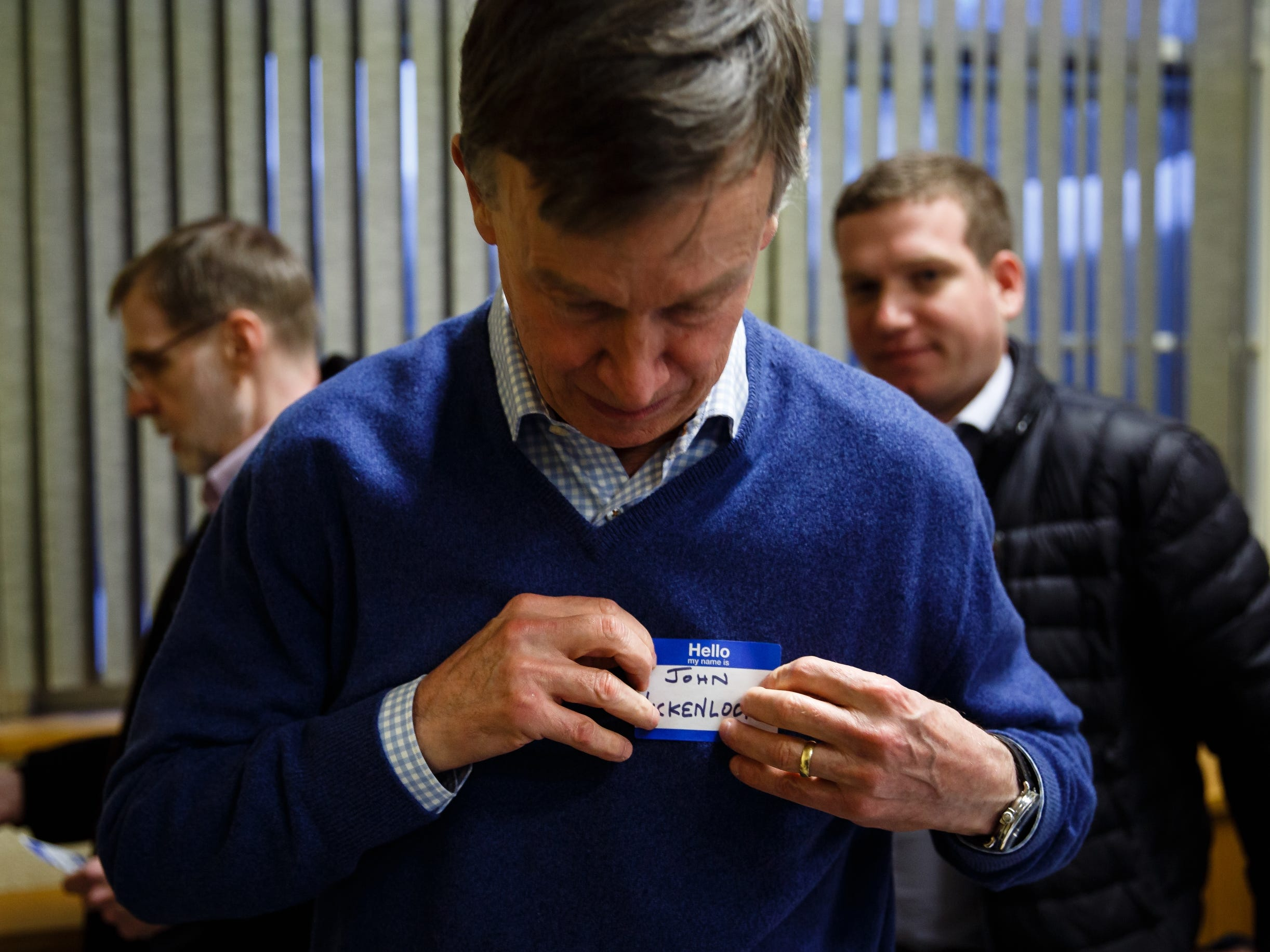 Former Governor of Colorado John Hickenlooper puts on a name tag as he walks into the Story County Democrats: Annual Soup Supper Fundraiser on Saturday, Feb. 23, 2019 in Ames.