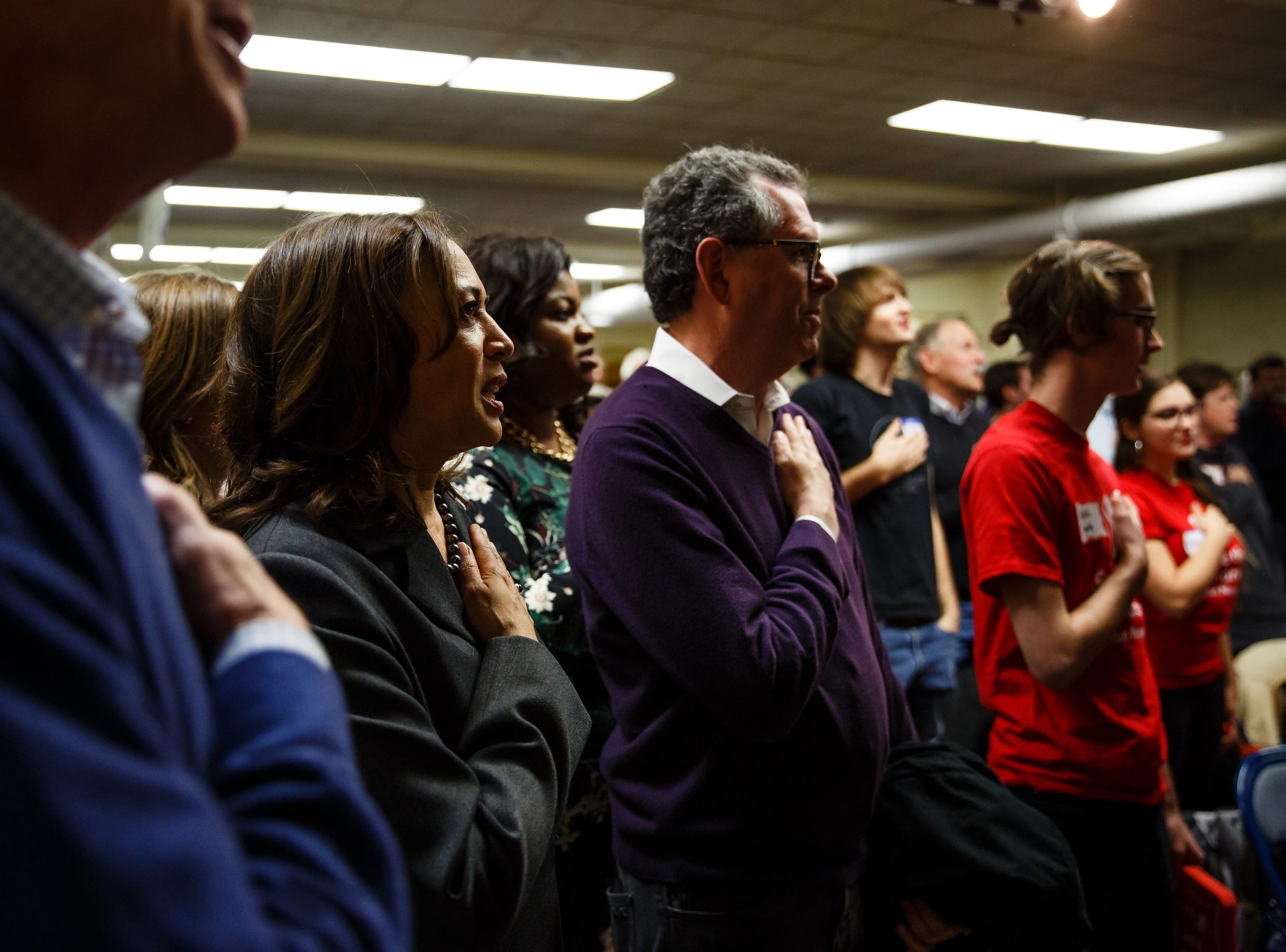 California Sen. Kamala Harris and former Governor of Colorado John Hickenlooper, far left, recite the Pledge of Allegiance at the Story County Democrats: Annual Soup Supper Fundraiser on Saturday, Feb. 23, 2019 in Ames.